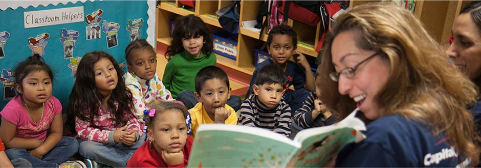 Capital One volunteer reading book to children